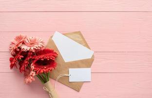 flores vermelhas gerbera margarida, envelope e etiqueta de etiqueta em branco rosa foto