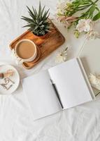 livro aberto, café e flores vista superior na cama branca. mock up design foto