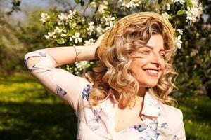 mulher sorridente de verão com chapéu de palha no parque foto