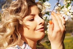 close-up de rosto feminino, mulher cheirando flores brancas foto