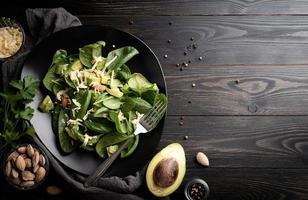 vista superior de abacate fresco de verão e salada de espinafre em madeira preta foto