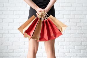 pernas de mulher com sacolas de compras no fundo branco foto