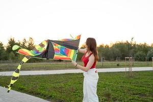 jovem empinando uma pipa em um parque público ao pôr do sol foto