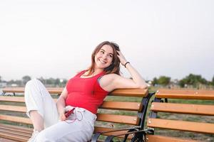 adolescente feliz sentada em um banco no parque ouvindo foto