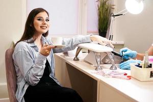 mulher fazendo manicure em um salão de beleza e segurando uma xícara de café branca foto