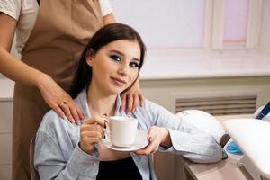 mulher fazendo manicure e massagem ao mesmo tempo em um salão de beleza foto