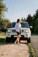 uma mulher em uma camisa branca ao lado de um carro branco na estrada foto