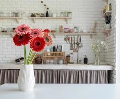 cozinha design de interiores vista frontal de brilhantes margaridas gerbera em um vaso foto