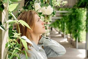 jovem de pé em rosas brancas em um jardim ou parque foto