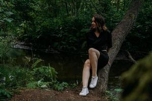 mulher com roupas pretas em uma floresta escura de coníferas. rastreamento e viagem foto