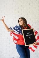 mulher com bandeira americana segurando cartaz com palavras feliz dia da independência e mostrando o símbolo da paz foto