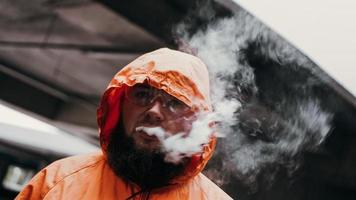um homem de óculos de segurança e um terno laranja. homem exala fumaça foto