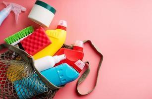 garrafas higiênicas e ferramentas de limpeza em bolsa de malha em fundo rosa foto