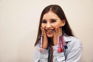 mulher sorrindo, segurando uma paleta de esmaltes de manicure e pedicure foto