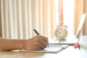 mão humana escrevendo no caderno na mesa de trabalho foto