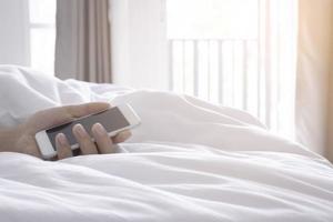 mão segurando o smartphone na cama branca pela manhã foto