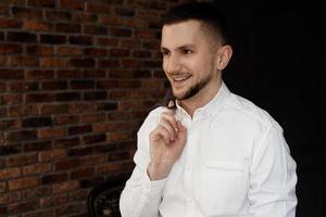 elegante jovem empresário de camisa branca segurando uma jaqueta no dedo foto