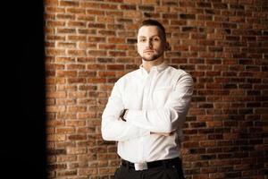 homem bonito com os braços cruzados em pé perto da parede de tijolo vermelho foto