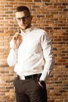homem bonito com óculos em pé perto de uma parede de tijolo vermelho foto