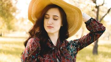 retrato, bela jovem usando chapéu de palha ao pôr do sol foto