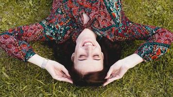 jovem mulher deitada na grama. pessoas relaxando ao ar livre. foto