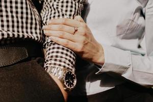 casal de amantes de mãos dadas. mão com relógio de pulso. foto