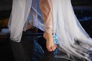 pernas femininas na água com salpicos. foto em uma luz neon