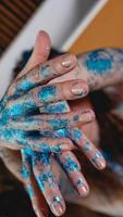 glitter azul nas mãos da mulher. movimentos suaves das mãos foto