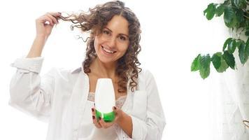 Mulher bonita mostrando tubo cosmético branco para cabelos cacheados na mão foto