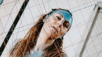 menina morena atrás da rede de fios. mulher com brilhos azuis foto