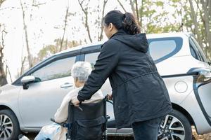 ajudar e apoiar paciente idosa asiática em cadeira de rodas obter carro foto