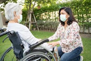 ajudar mulher idosa asiática em cadeira de rodas foto