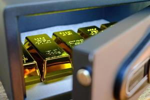 caixa de cofres de aço cheia de pilhas de moedas e barra de ouro na mesa de madeira foto