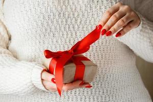presente com uma fita vermelha nas mãos sobre um fundo branco foto