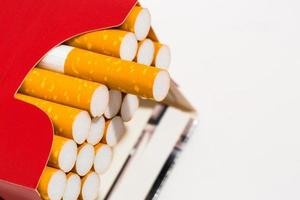 caixa vermelha cheia de cigarros no isolado foto