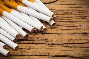 pilha de cigarro no fundo da mesa de madeira foto