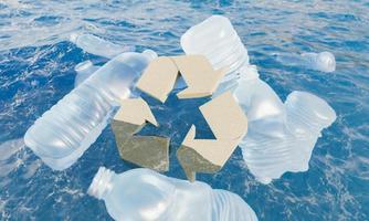 garrafas de plástico flutuando no mar com símbolo de reciclagem de cortiça foto