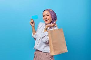 retrato de uma mulher alegre segurando sacolas de compras e cartão de crédito foto