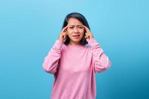 retrato de mulher asiática tocando sua cabeça e expressando preocupação foto