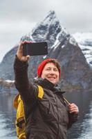 homem tirando uma selfie com montanhas atrás dele foto