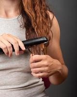 uma garota com cabelo encaracolado alisa os fios com ferro, cuidados com os cabelos. foto