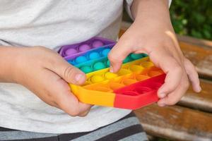 criança brincando com covinha simples de brinquedo educacional colorido. foto