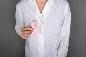 médico segurando um símbolo de fita rosa da luta contra o câncer de mama. foto