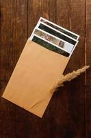 as fotos estão dentro de um envelope bege, localizado em uma mesa de madeira marrom