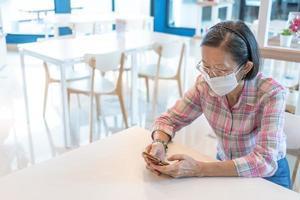 mulher madura usando máscara em um café foto