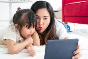 mãe e filha assistindo a um desenho animado em um tablet foto