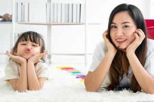 mãe e filha deitadas no tapete foto