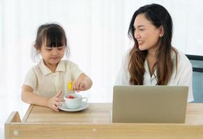 mãe e filha em uma mesa com um laptop foto