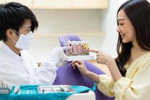 dentista ensinando paciente sobre higiene dentária na clínica foto