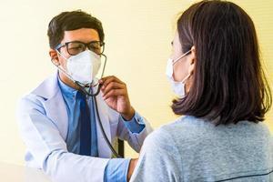 médico usando estetoscópio para ouvir os batimentos cardíacos do paciente foto
